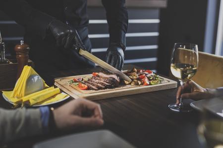 Lo chef del ristorante affetta una bistecca di manzo mediamente cotta e serve la specialità della casa agli ospiti