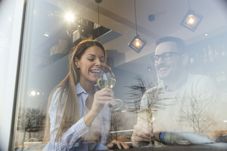 Portrait of a young couple in love on a date,  sitting at a restaurant table, drinking wine
