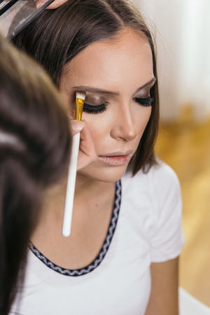 Make up artist working in a make up studio, shading the female client's eyelids