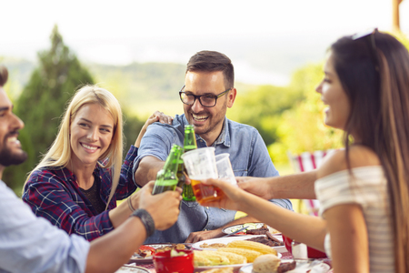 Group of young friends having an outdoor barbecue lunch, making a toast while sitting at the table, drinking beer and having fun