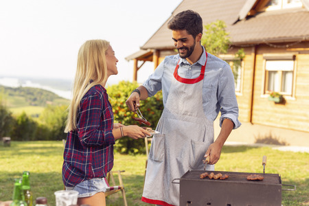 Couple making a backyard barbecue party on a sunny summer day, grilling meat and having fun 写真素材