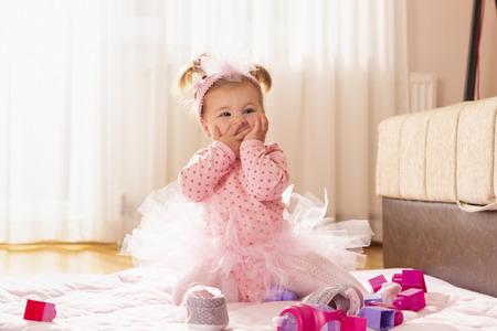 Beautiful little baby girl sitting on the nursery floor, sending kisses with her hands Reklamní fotografie - 119390349