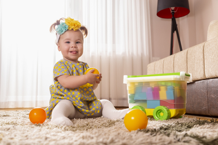 Beautiful little baby girl, sitting on a carpet on the nursery floor, playing and throwing a ball