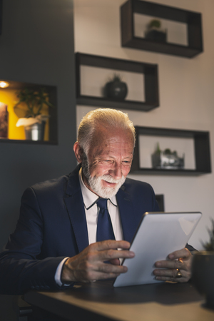 Senior businessman in a restaurant, working on a tablet computer