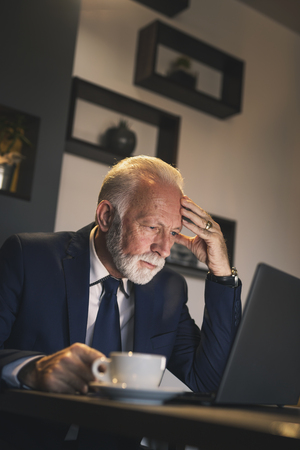 Senior businessman in a restaurant, working on a laptop computer and having a cup of coffee Imagens