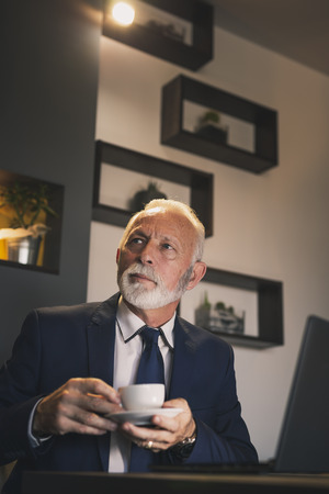Senior businessman in a restaurant, working on a laptop computer and having a cup of coffee 스톡 콘텐츠