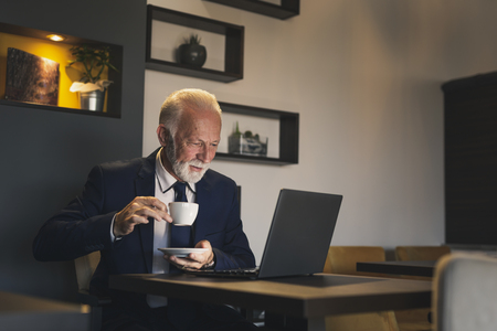 Senior businessman in a restaurant, working on a laptop computer and having a cup of coffee Reklamní fotografie
