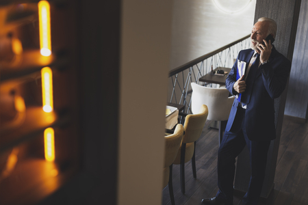 Senior businessman standing in a modern office building restaurant, having a phone conversation and holding some document folders 스톡 콘텐츠