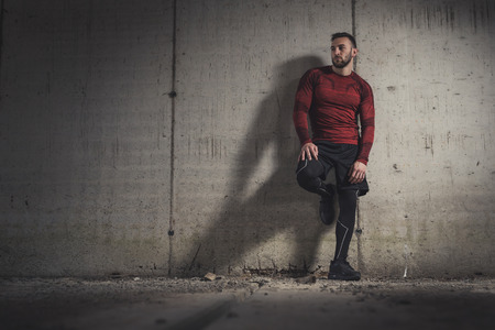 Muscular athletic man wearing sportswear, taking a workout break, standing and leaning on a concrete wall, pensive