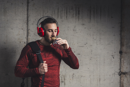 Muscular athletic man wearing sportswear and carrying a gym bag, listening to the music and eating a protein bar after a hard workout