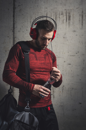 Muscular athetic man wearing sportswear and carrying a gym bag, listening to the music and drinking water while going to a gym Reklamní fotografie