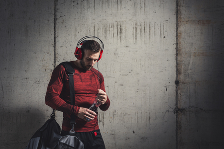 Muscular athetic man wearing sportswear and carrying a gym bag, listening to the music and drinking water while going to a gym Imagens
