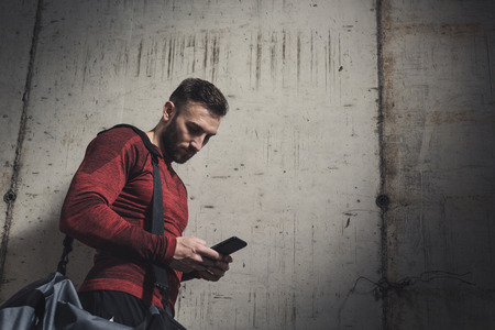 Athletic young man standing next to a concrete wall, wearing sportswear and carrying a gym bag, typing a text message on a smart phone