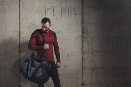 Muscular athetic man wearing sportswear and carrying a gym bag, going to a gym for a workout session