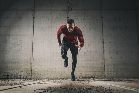 Young, athletic man working out on a construction site in front of a concrete wall, starting a sprint
