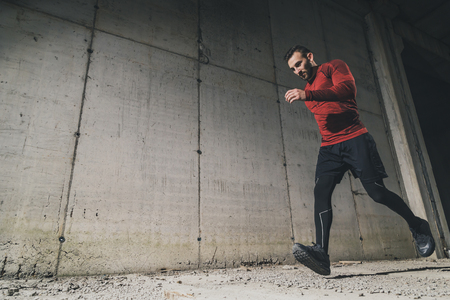 Young, athletic man working out on a construction site, jogging next to a concrete wall