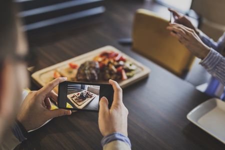 Couple sitting at a restaurant table, taking photos of food they have ordered before lunch 스톡 콘텐츠
