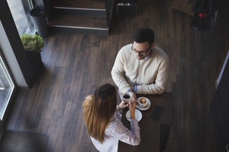 High angle view of a young couple in love on a date, standing next to a restaurant counter, drinking coffee and having a conversation