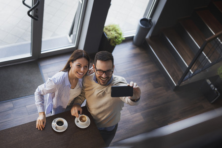 High angle view of a young couple in love on a date, standing next to a restaurant counter, taking a selfie Imagens