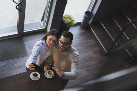 High angle view of a young couple in love on a date, standing next to a restaurant counter, taking a selfie Reklamní fotografie