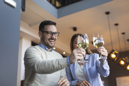 Young couple in love on a date, standing next to a restaurant counter, raising glasses of wine and making a toast while waiting for a table Imagens