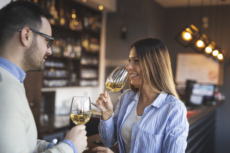 Young couple in love on a date, standing next to a restaurant counter, drinking wine and having a pleasant conversation while waiting for a table for lunch