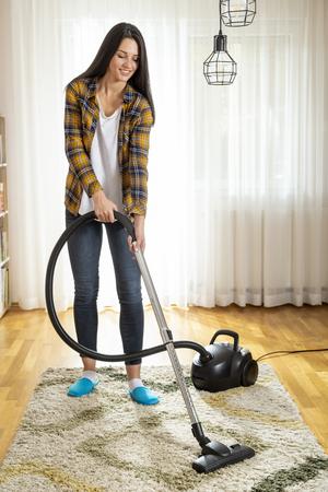 Giovane donna che fa le faccende domestiche, passa l'aspirapolvere sul tappeto del soggiorno