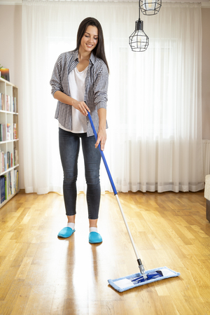 Woman holding a floor wiper and wiping floor, keeping the daily home hygiene and doing housework Imagens