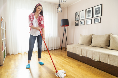 Woman holding a floor wiper and wiping floor, doing home chores and keeping the daily home hygiene