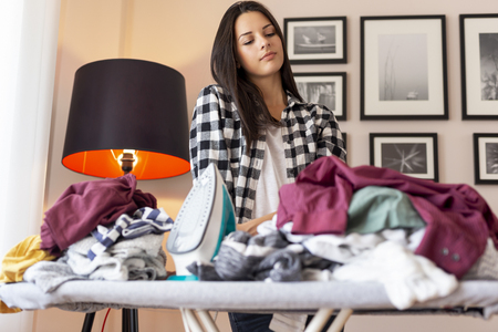 Young bored and tired woman leaning on the ironing board, surrounded with bunch of wrinkled clothes ready for ironing