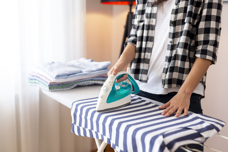 Detail of female hands holding the iron, ironing washed, wrinkled clothes on the ironing board Reklamní fotografie