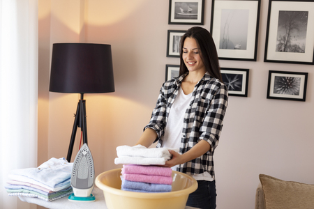 Beautiful young woman standing next to an ironing board, folding clean, ironed towels into a washbowl