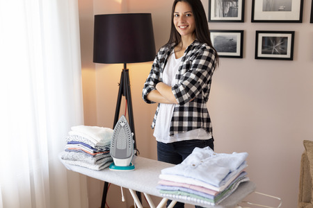 Beautiful young woman standing next to an ironing board, taking a break after ironing and folding clean wrinkled clothes Imagens