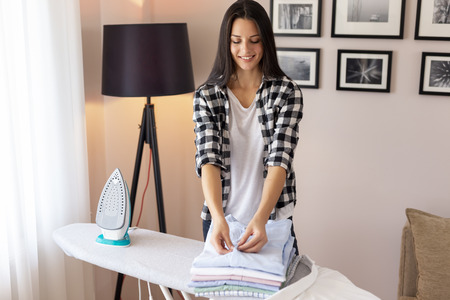 Woman folding clean clothes on the ironing board after doing the ironing