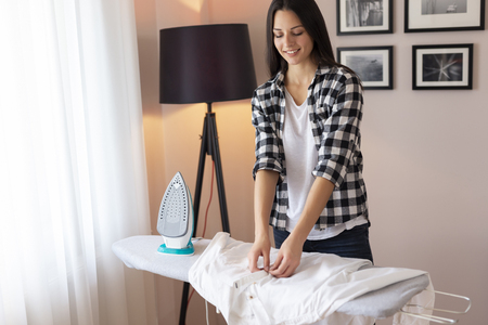 Woman folding clean ironed shirt on the ironing board after doing the ironing 스톡 콘텐츠