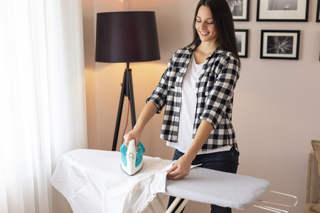 Beautiful young woman standing next to an ironing board, doing the ironing