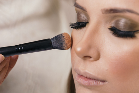 Make up artist doing the model's make up, applying the face powder with a make up brush