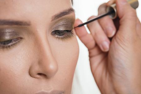 Make up artist working in a make up studio, applying eyeliner on female clients eyelids