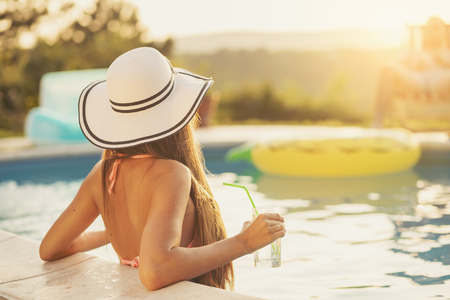 Attractive young woman wearing bikini and a hat, standing in the swimming pool, enjoying beautiful summer sunset, looking away from the camera