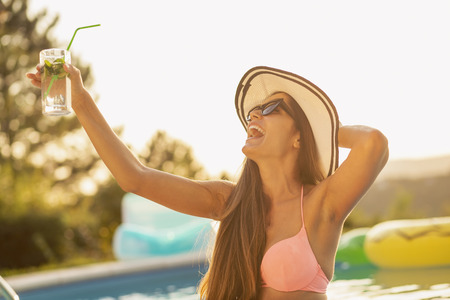 Attractive young woman wearing bikini and a hat, standing in the swimming pool, drinking cocktails and making a toast Imagens