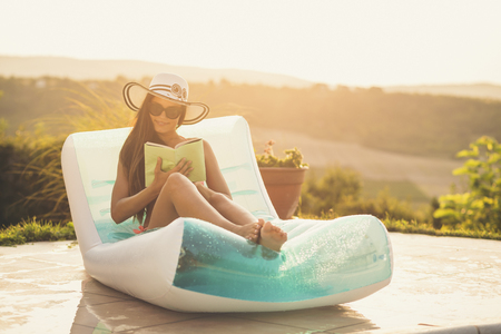 Attractive young woman wearing bikini and a hat, lying on an air matress by the swimming pool, drinking cocktails and reading a book