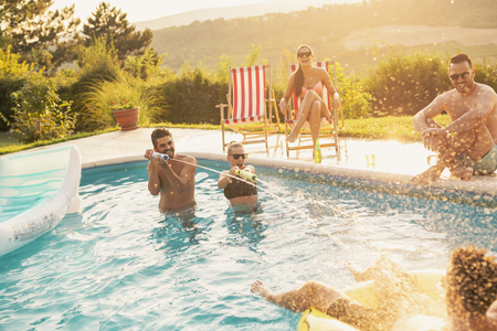 Group of friends at a poolside summer party, having fun in the swimming pool, drinking beer and splashing water