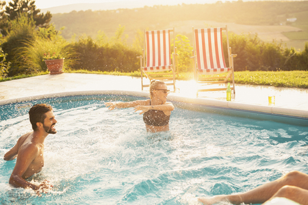Group of friends at a poolside summer party,  having fun in the swimming pool, splashing water Reklamní fotografie