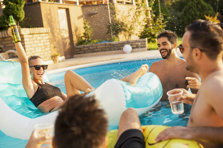 Group of friends at a poolside summer party, having fun in the swimming pool, drinking cocktails and beer and making a toast