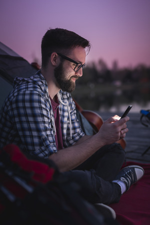 Young man camping on the lake docks, sitting on the tent entrance and typing a text message