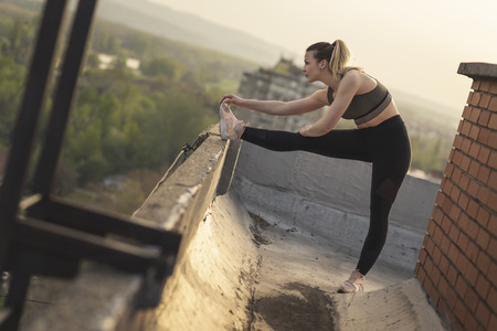 Beautiful young woman in sportswear stretching out before workout on a building rooftop terrace 版權商用圖片