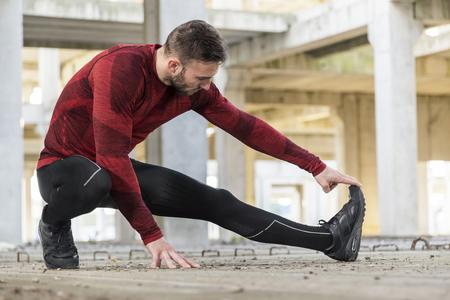 Athletischer, muskulöser Mann, der sich für ein Training ausstreckt und aufwärmt