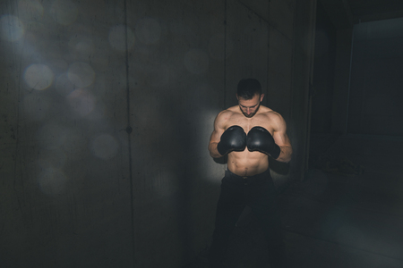 Fit muscular boxer wearing boxing gloves, preparing for a competition