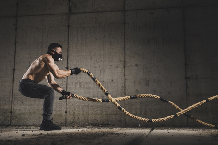 Athletic, muscular man wearing training mask and doing battle ropes functional training, making waves with the ropes, exercising strength