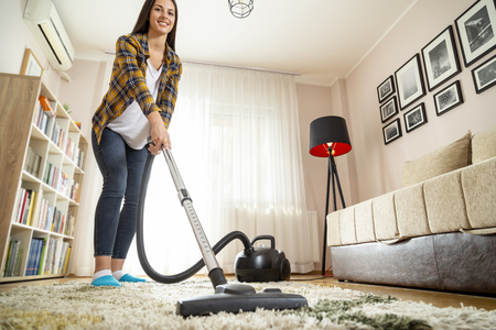 Young woman doing home chores, vacuuming the living room carpet Imagens